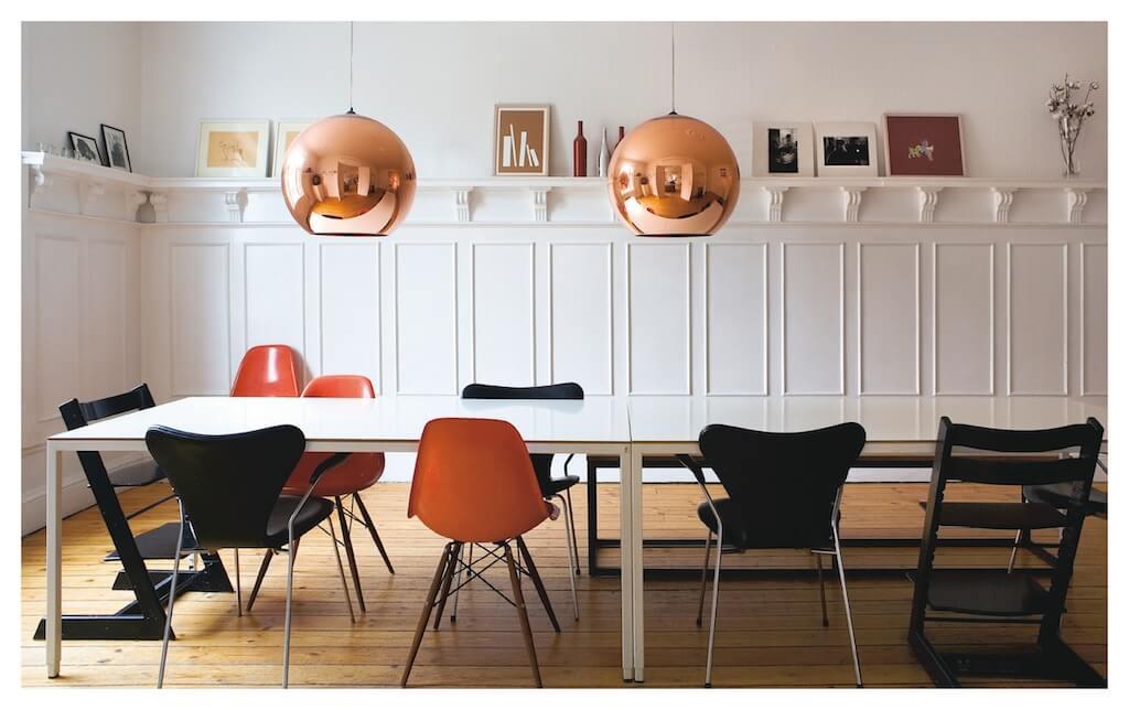 """Sir Conran zeigt in seinem Buch """"Einfach entspannt wohnen"""" Esszimmer mit Kupferlampen und unterschiedlichen Vintage Stühlen"""