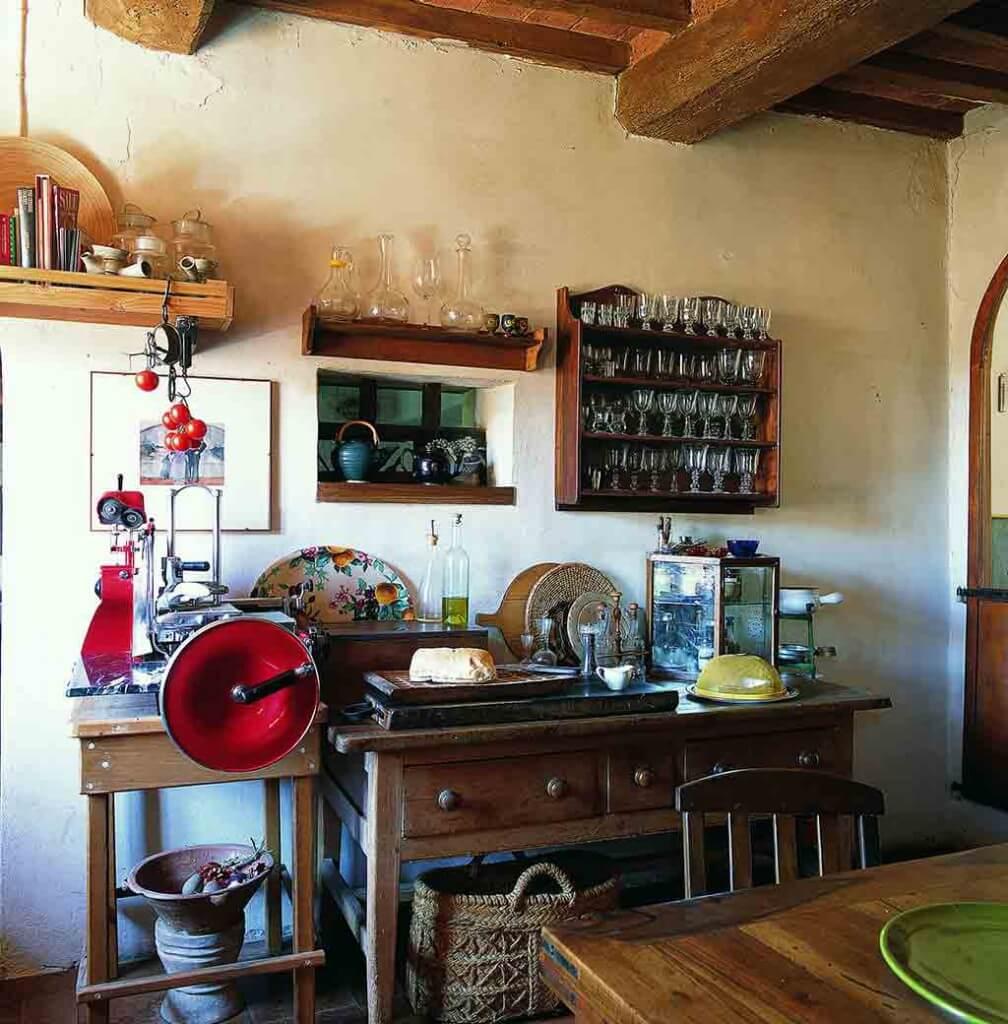 Typische Landhausküche in Italien mit dunklen Holzmöbeln und alter roter Aufschnittmaschine