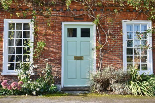 Türen in hellen Pastellfarben oder Weiß sind typisch für Häuser im frischen zeitlosen Landhauslook