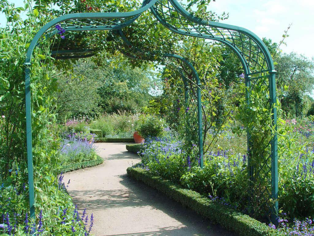 Mit Mauern, Hecken und Formgehölzen werden verträumte Gartenräume geschaffen, in denen eine üppige Pflanzenvielfalt blüht.