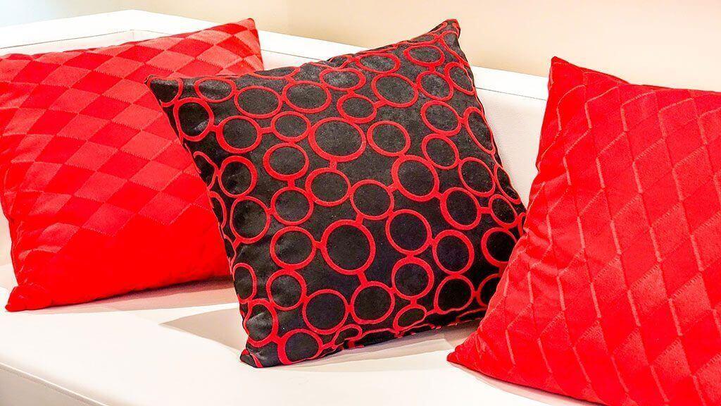 Rote Kissen und grafische Muster bringen Leben auf ein weißes Sofa