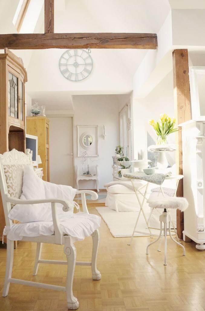 Französischer Landhausstil unter dem Dach mit weißen Möbeln, hohen Decken und naturbelassenen Holzbalken