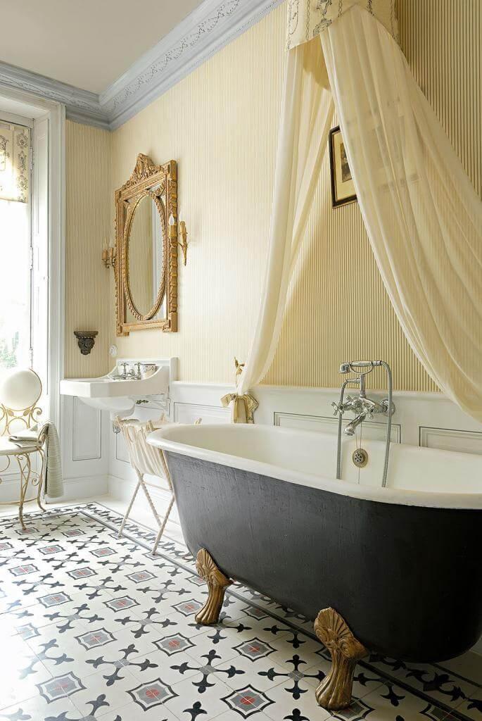 Die Badewanne aus dem Jahr 1900 erstrahlt mit neuem Anstrich und steht unter einem romatischen Betthimmel